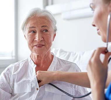 רופאה בודקת דופק לאישה מבוגרת