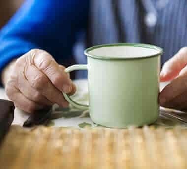 יד מבוגרת מחזיקה ספל